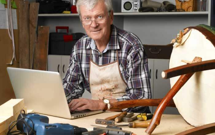 Portrait of retired carpenter sitting at his workshop and working with laptop next to the broken away legged chair. Small business.