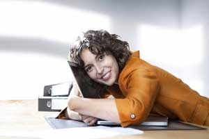 Businesswoman hugging laptop in office, smiling, portrait