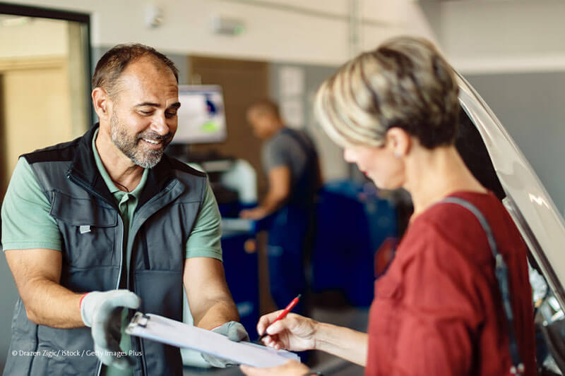 Auftragswert Gelbe Seiten Symbolbild Frau unterscheibt Vertrag in Autowerkstatt